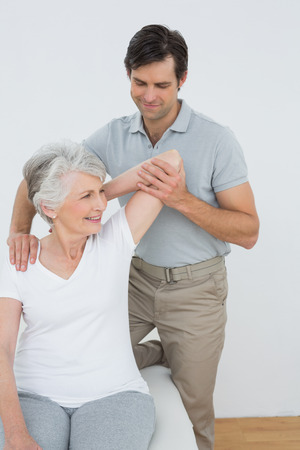 old man on a physical pressure: Male physiotherapist stretching a smiling senior womans arm in the medical office