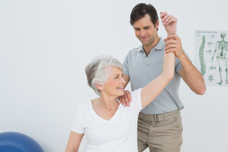 Male physiotherapist stretching a smiling senior womans arm in the medical office