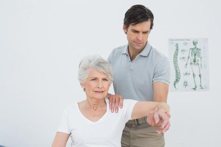 Männlich Physiotherapeut Strecken einer älteren Frau am Arm in der Arztpraxis