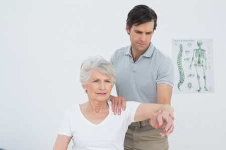 Male physiotherapist stretching a senior womans arm in the medical office
