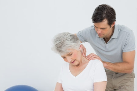 back sprains: Male physiotherapist massaging a senior womans neck in the medical office
