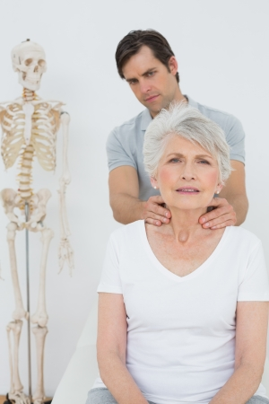 Male physiotherapist massaging a senior womans neck in the medical office