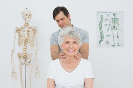 Male physiotherapist massaging a senior woman's neck in the medical office photo