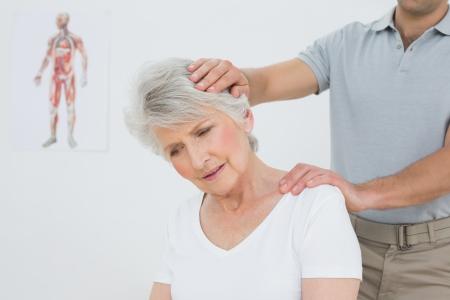 年配の女性診療所で行われる首の調整を取得 写真素材 - 25505755