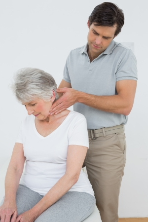Male physiotherapist massaging a senior womans neck in the medical office photo