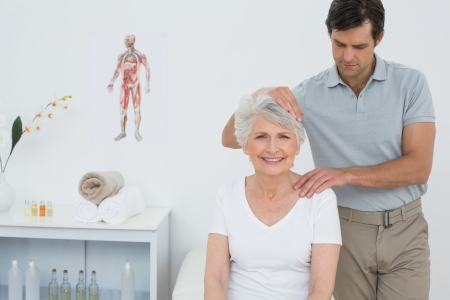 old man on a physical pressure: Senior woman getting the neck adjustment done in the medical office