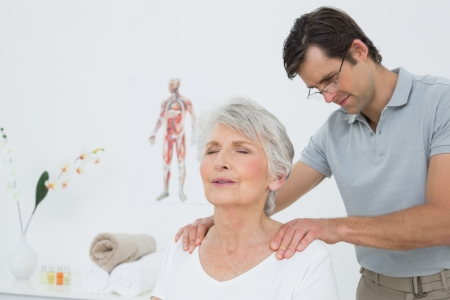 Male physiotherapist massaging a senior womans shoulders in the medical office Stock Photo