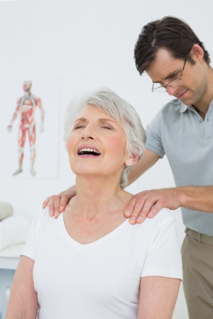 Male physiotherapist massaging a senior woman's shoulders in the medical office photo