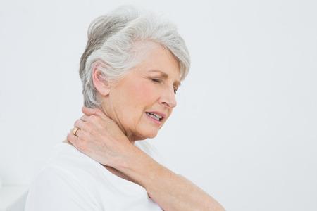 dolor muscular: Primer plano vista lateral de una mujer mayor que sufre de dolor de cuello sobre fondo blanco Foto de archivo