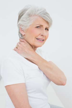 neck pain: Side view portrait of a senior woman suffering from neck pain over white background Stock Photo