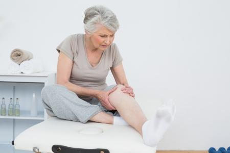 dolor de rodilla: Superior de la mujer con las manos en una rodilla dolorosa mientras se está sentado en la mesa de examen