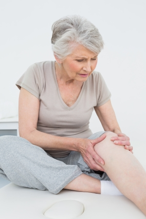 injure: Senior woman with her hands on a painful knee while sitting on examination table Stock Photo