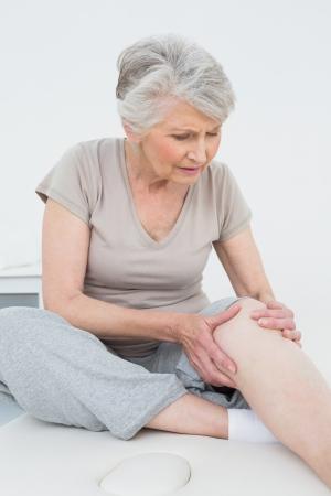 de rodillas: Superior de la mujer con las manos en una rodilla dolorosa mientras se está sentado en la mesa de examen