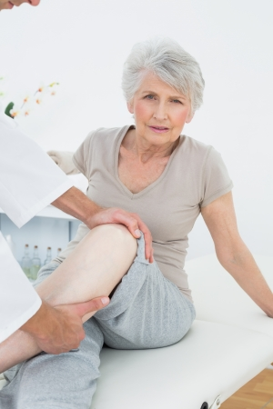 Portrait of a senior woman getting her leg examined at the medical office Reklamní fotografie