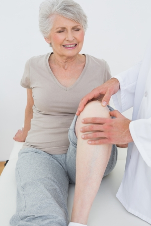 Displeased senior woman getting her knee examined at the medical office Stock Photo