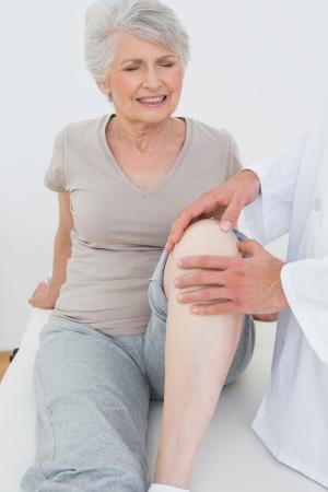 Verärgert ältere Frau, die ihr Knie an der Arztpraxis untersucht