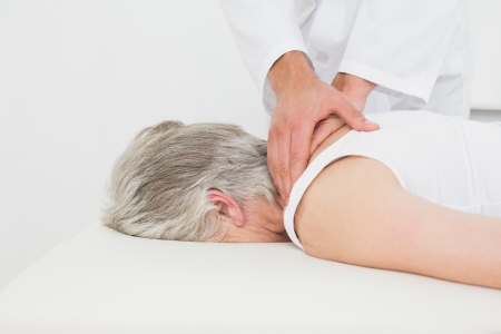 back sprains: Close-up of a physiotherapist massaging a senior womans back in the medical office Stock Photo