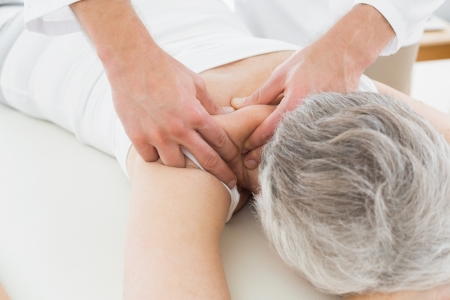 spinal conditions: Close-up of a physiotherapist massaging a senior womans back in the medical office Stock Photo