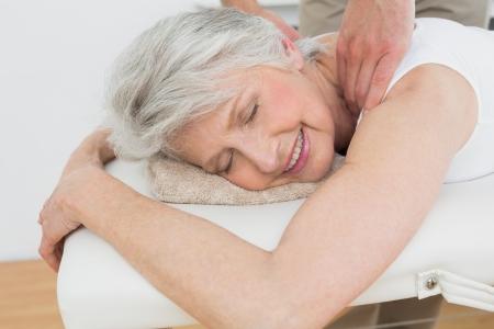 Fisioterapeuta masculino masajear los hombros de una mujer mayor en el consultorio médico Foto de archivo