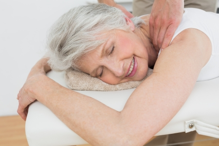 Male physiotherapist massaging a senior womans shoulder in the medical office photo