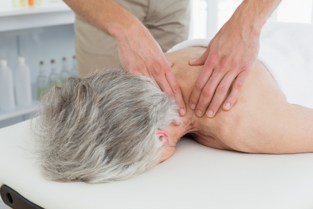Close-up of a physiotherapist massaging a senior womans back in the medical office photo