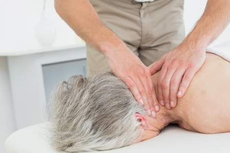 Close-up of a physiotherapist massaging a senior womans neck in the medical office photo