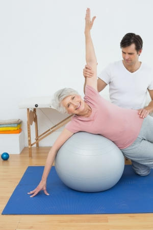 Physical therapist assisting senior woman with yoga ball in the gym at hospital Stock Photo