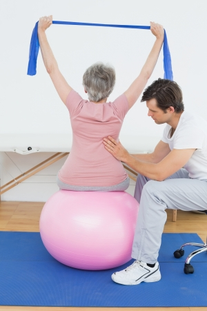 yoga to cure health: Senior woman sitting on yoga ball while working with a physical therapist Stock Photo