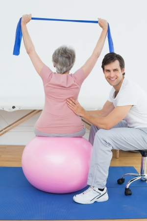 Senior woman sitting on yoga ball while working with a physical therapist photo