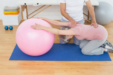 Side view of a physical therapist assisting senior woman with yoga ball in the gym at hospital Stock Photo