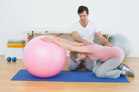 physical therapist: Side view of a physical therapist assisting senior woman with yoga ball in the gym at hospital Stock Photo
