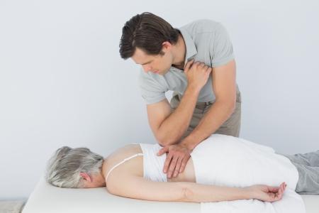 spinal manipulation: Maschio fisioterapista che massaggia la schiena di una donna senior presso l'ufficio medico