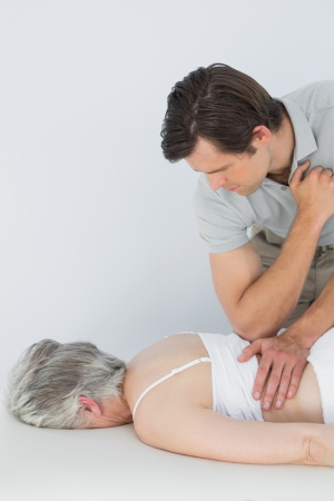 back sprains: Male physiotherapist massaging a senior womans back in the medical office
