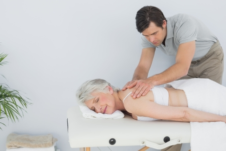 spinal manipulation: Male physiotherapist massaging a senior womans back in the medical office