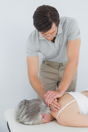 Male physiotherapist massaging a senior woman's back in the medical office photo
