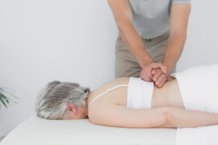 Male physiotherapist massaging a senior womans back in the medical office