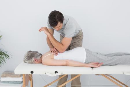 Männlich Physiotherapeut massiert Rückseite eines älteren Frau in der Arztpraxis