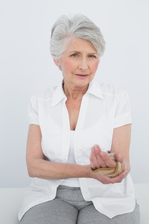 Portrait of a senior woman with hand in wrist brace sitting in the medical office photo