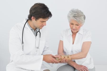 医療事務に年配の女性の手首を調べる男性理学療法士