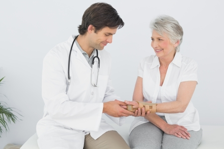 orthopaedic: Male physiotherapist examining a senior womans wrist in the medical office