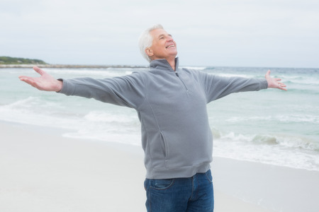 arms  outstretched: Casual senior man with arms outstretched standing at the beach