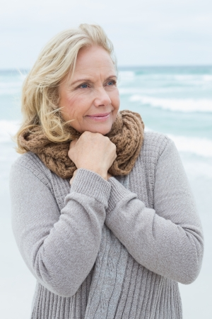 Contemplative casual senior woman looking away at the beach