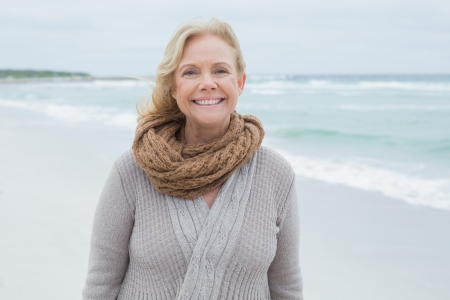 fair woman: Portrait of a smiling casual senior woman relaxing at the beach