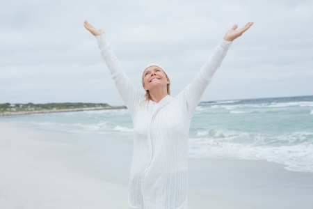 arms  outstretched: Casual senior woman with arms outstretched standing at the beach