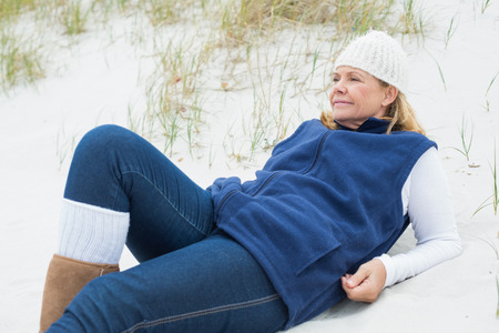 contemplative: Relaxed contemplative casual senior woman looking away at the beach