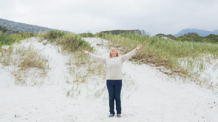 arms  outstretched: Full length of a senior woman with arms outstretched standing at the beach Stock Photo