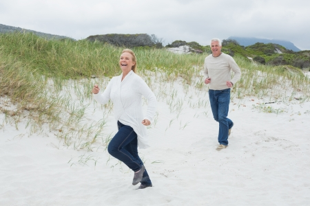 Full length of a cheerful senior couple running at the beach