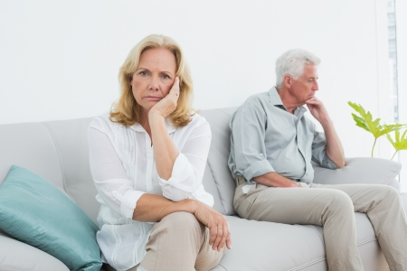displeased: Displeased relaxed senior couple sitting on sofa in a house