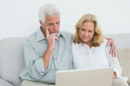 Relaxed loving senior couple using laptop on sofa in a house photo