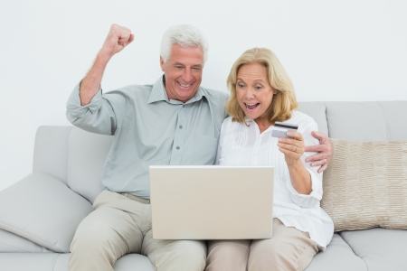 Cheerful senior couple doing online shopping through laptop and credit card on sofa in a house photo